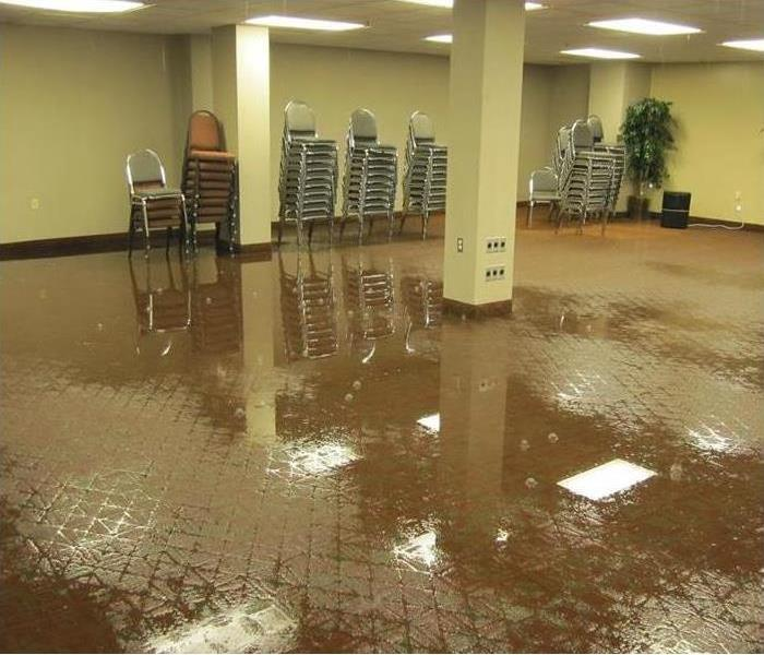 Standing water in the middle of a large room with chairs stacked in back