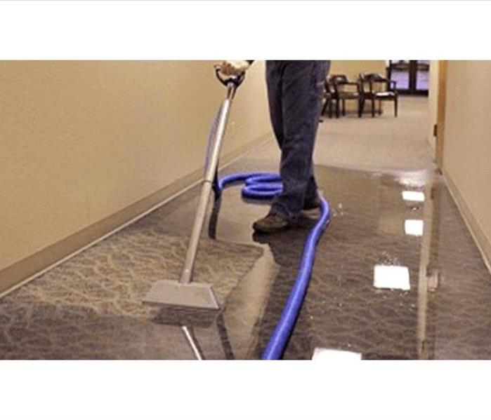 Removing water from wet floor with a vacuum
